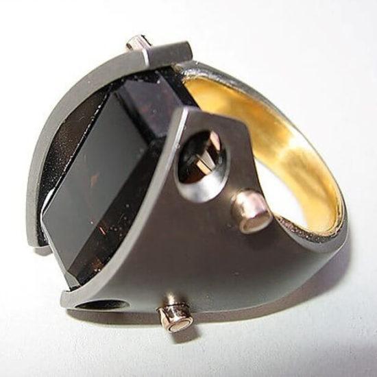 Pierścień męski. Praca na prywatne zamówienie w 2008 roku. Wykonana ze srebra rutenowanego i złota z topazem.