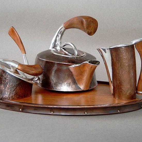 Komplet herbaciany. Został wykonany z miedzi, srebra i drewna orzechowego, składa się z czajnika o pojemności 1 litra, łyżeczki, mlecznika, cukierniczki i tacy. Został wykonany i sprzedany do kolekcji prywatnej.